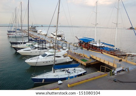 Yacht-club over blue nature scene, row of luxury sailboats reflected in water - stock photo