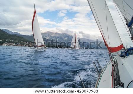 "Yacht going under a bias. Tivat, Montenegro - 27 April, 2016 Regatta ""Russian stream"" in God-Katorskaya bay of the Adriatic Sea off the coast of Montenegro. - stock photo"