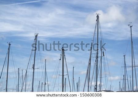Yacht masts against blue Summer sky - stock photo