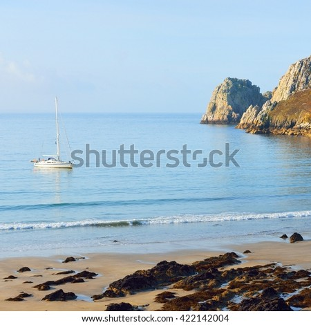 Yacht on anchor in a bay of Celtic sea at the coast of Brittany