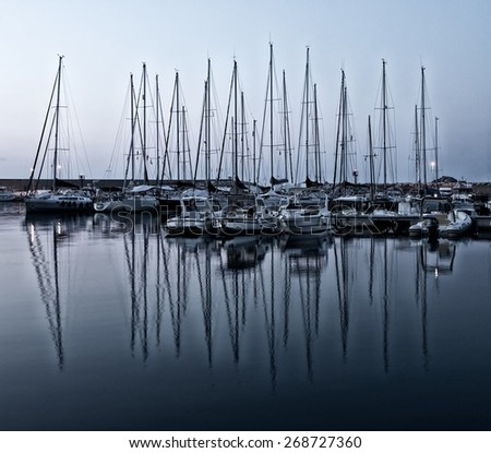 Yacht pier in late evening light. Sunset.View to pier. Yachts with reflections. Silhouette of yachts poles and reflections in the water in blue evening light, night scene, darkness - stock photo