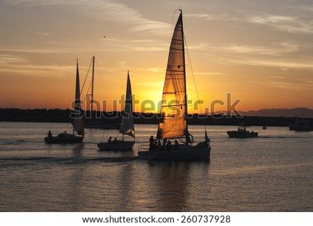 Yacht quietly returned to the place of chartering. The setting sun shines through the sail. - stock photo