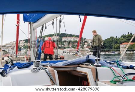 "Yacht Rigging and three men. Tivat, Montenegro - 24 April, 2016 Regatta ""Russian stream"" in God-Katorskaya bay of the Adriatic Sea off the coast of Montenegro. - stock photo"
