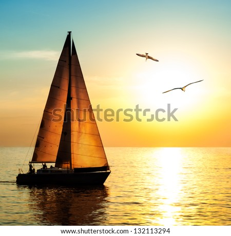 Yacht sailing against sunset. Holiday lifestyle landscape with skyline sailboat and two seagull. Yachting tourism - maritime evening walk. Romantic trip on luxury yacht during the sea sunset. - stock photo