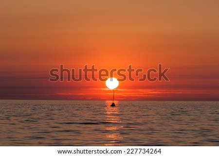Yacht sailing against sunset. Romantic trip on luxury yacht during the sea sunset. - stock photo