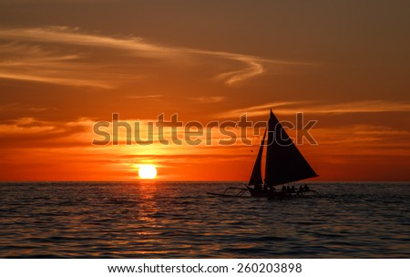 Yacht sailing against sunset. Yachting tourism - maritime evening walk. Romantic trip on  yacht during the sea sunset. - stock photo