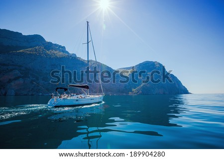 Yacht sailing along the shore the sea in calm weather. - stock photo