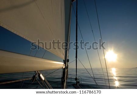 Yacht sailing at sunset - stock photo