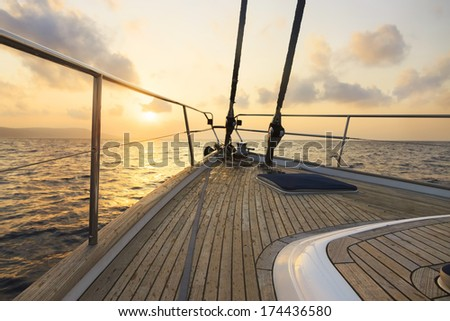 Yacht sailing at sunset - stock photo