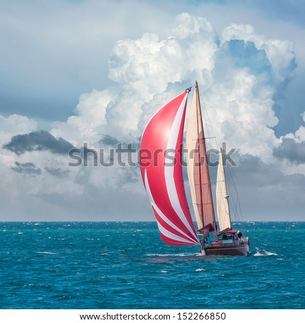 Yacht sailing at waves of the sea. Nautical landscape with sailboat - cruising yacht sailing under full sail taking part in regatta race. Yachting - maritime romantic trip on the yacht with red sails. - stock photo