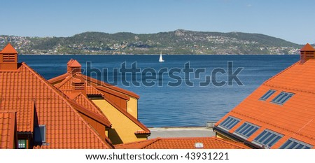 Yacht sailing in a sea on sunny day. Bright roofs of houses are in the foreground.