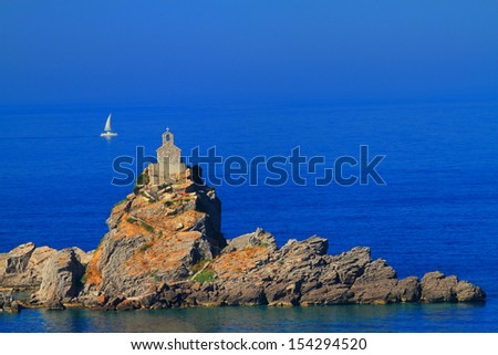 Yacht sailing on Mediterranean sea beyond the stone church built in top of an island