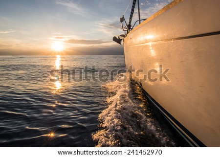 Yacht sailing towards sunset at sea - stock photo