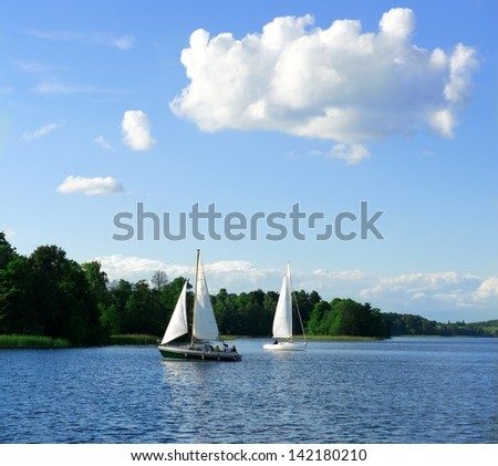 Yacht sailing towards sunset in blue background,sunny background, yacht in a lake at the evening,yacht and blue water sea,yacht sailing in sunset.Blue sunset evening background, yacht,Lithuania,Trakai - stock photo