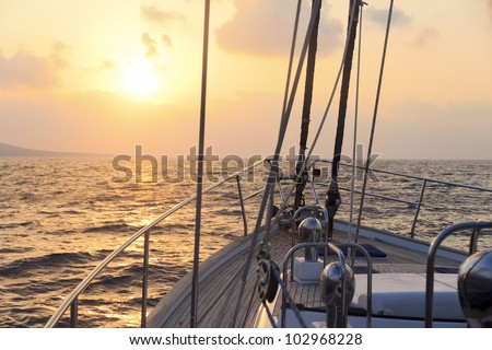 Yacht sailing towards the sunset - stock photo