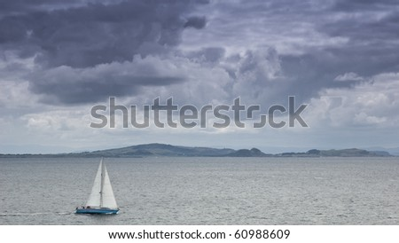 yacht sailing under heavy clouds - stock photo
