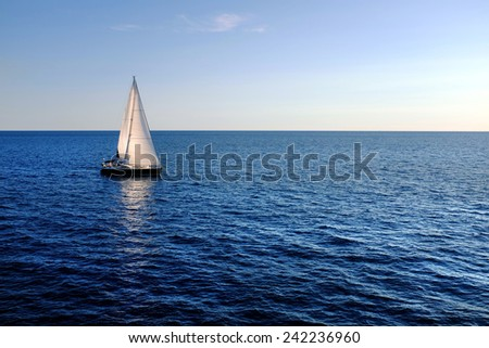 Yacht with reflection sailing on open sea.