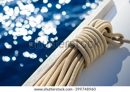 Yachting detail - Rope on deck / board with water and sun reflection in background - stock photo