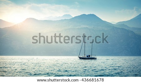 Yachting. Landscape panorama with yacht sailer ship sailing by lake or sea waves in evening sunset sun sunbeams. Fishing sporting poat on water. Mountains background. Garda Lake, Veneto region, Italy - stock photo