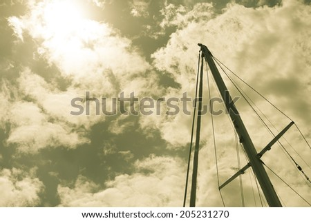 Yachting. Sailboat view of different parts of yacht. Mast against blue sky. Sepia tone - stock photo