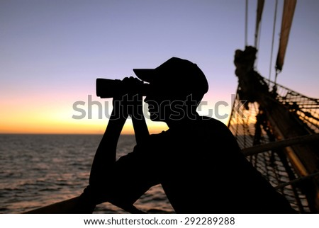 Yachting. Sailing ship. A young man looking through binoculars at sunset - stock photo
