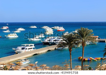 Yachts, and beach area with sun shades and lounging chairs at a resort on the Red Sea in Hurghada, Egypt - stock photo
