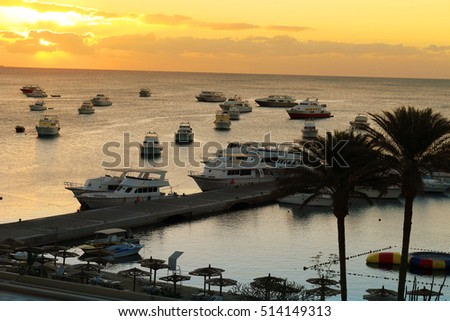 Yachts, and beach area with sun shades and lounging chairs at a resort on the Red Sea in Hurghada, Egypt at sunset