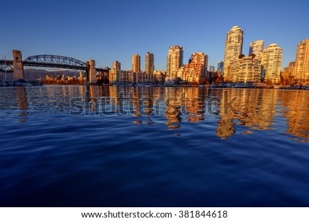 Yachts and bridge on the left side, illuminated buildings on the right side, and calm river - stock photo