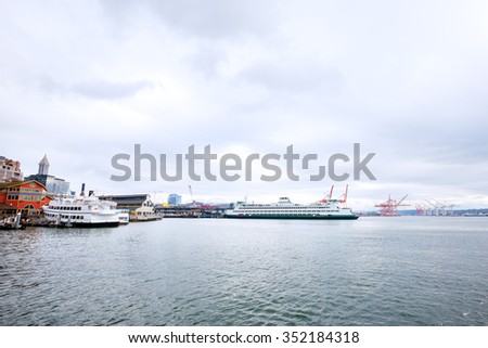 yachts and liner along dock on sea in cloudy sky