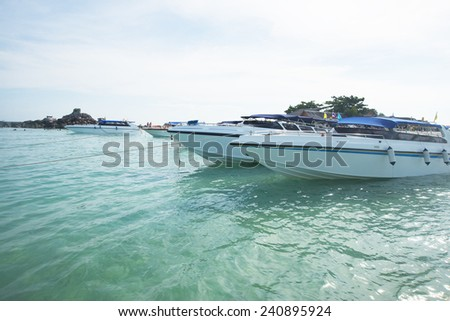 Yachts and motor boats moored in the marina at Islands Thailand  stand on blue clear water texture against sky with clouds and stone mountain Transportation and speed concept - stock photo