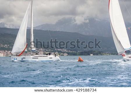"Yachts are deployed near the buoy. Tivat, Montenegro - 28 April, 2016. Regatta ""Russian stream"" in God-Katorskaya bay of the Adriatic Sea off the coast of Montenegro. - stock photo"