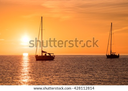 Yachts in the sea at sunset, Yachting. Romantic trip on luxury yacht during the sea sunset. - stock photo