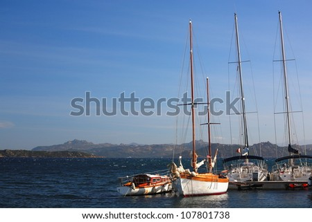 Yachts moored in a Mediterranean bay with coastal mountains and blue sky - stock photo