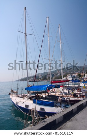 Yachts moored on the waterfront of the seaside city - stock photo
