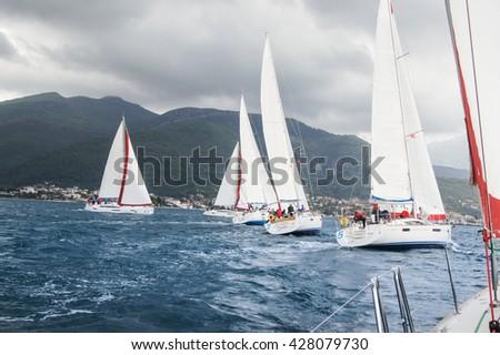 "Yachts with teams. Tivat, Montenegro - 28 April, 2016 Regatta ""Russian stream"" in God-Katorskaya bay of the Adriatic Sea off the coast of Montenegro. - stock photo"