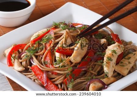 Yakisoba with chicken and vegetables on a plate and teriyaki sauce closeup. horizontal  - stock photo