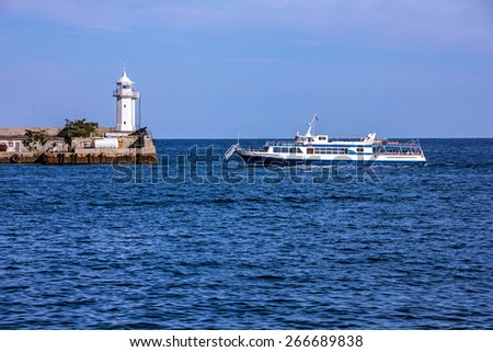 Yalta, Crimea, Russia. Tourist cutter and lighthouse.