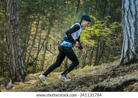 "Yalta, Russia - November 2, 2015: male athlete climbs a steep hill in woods during Mountain marathon ""Vertical kilometre AI-Petri"""