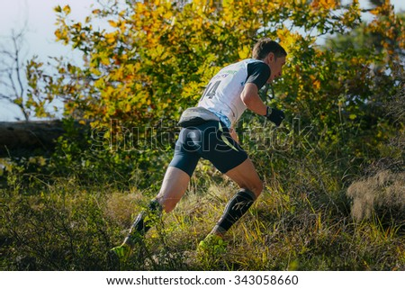 Yalta, Russia - November 4, 2015: young male runner running uphill, around autumn landscape during mountain marathon Tauris