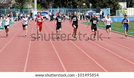 YALTA, UKRAINE - APRIL 25: Unidentified boys age 16-17 on the 100 meters race on Ukrainian Junior Track and Field Championships on April 25, 2012 in Yalta, Ukraine. - stock photo