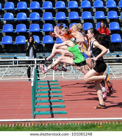 YALTA, UKRAINE - APRIL 25: Unidentified girls age 16-17 on the 100 meters hurdles race on Ukrainian Junior Track and Field Championships on April 25, 2012 in Yalta, Ukraine. - stock photo