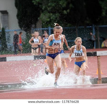 YALTA, UKRAINE - JUNE 01: Unidentified girls compete in the 3.000 Meter Steeplechase  on Ukrainian Track & Field Championships on June 01, 2012 in Yalta, Ukraine. - stock photo