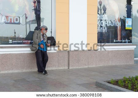 Yalta, Ukraine - May 23, 2013: Elderly homeless man begging for some money near sport shop on a sea-front