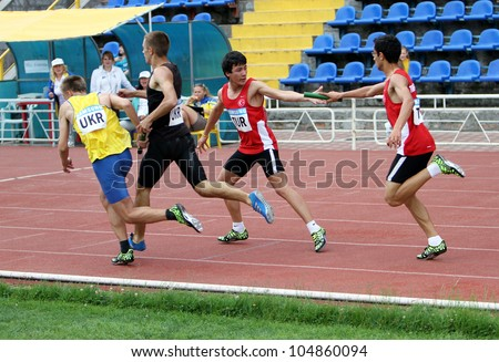 YALTA, UKRAINE - MAY 25: (L-R) Pozdniakov Oleksei, Pozhar Dmitro, Altintash Batuhan, Uznal Enis on relay race on the athletic meet between UKRAINE, TURKEY, BELARUS on May 25, 2012 in Yalta, Ukraine - stock photo