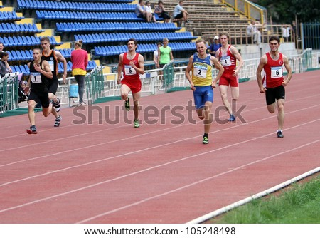YALTA, UKRAINE - MAY 25 : Unidentified athletes at the finish of 400 meters race on international athletic meet between Ukraine, Turkey, Belarus on May 25, 2012 in Yalta, Ukraine . - stock photo