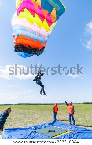 Yalutorovsk, Russia - May 24, 2008: Competition of parachutists on landing accuracy on sport airdrome. Paratrooper woman descends - stock photo