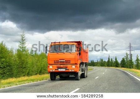 YAMAL, RUSSIA - AUGUST 5, 2012: Orange KAMAZ 6522 dump truck at the interurban road.