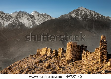 Yamchun Fort is the most visually prominent historic site in the Wakhan Valley in Gorno-Badakhshan Autonomous Province, Tajikistan. The mountains in the distance are in Afghanistan.  - stock photo