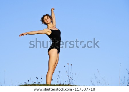 Yang ballet woman in training suit performs outdoor in sunset time. - stock photo