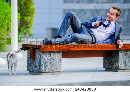 Yang businessman relaxing outdoors in the bench. - stock photo